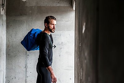 Athlete holding bag at concrete wall - p300m1587313 by Daniel Ingold