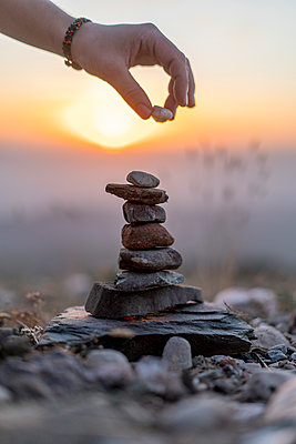 Close-up of man's hand placing stone on cairn at sunset - p300m2058586 von VITTA GALLERY