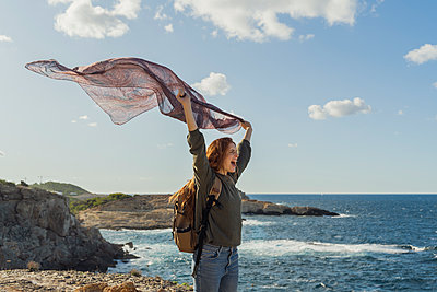 Happy redheaded young woman holding a cloth at the coast, Ibiza, Spain - p300m2159836 von VITTA GALLERY