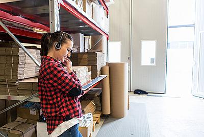 Determined female manual worker wearing headphones while using digital tablet at warehouse - p426m1580255 by Kentaroo Tryman
