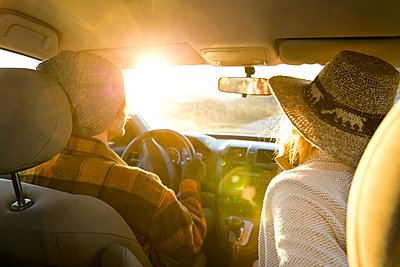 Rear view of young couple in car, sunlight on windscreen - p429m1118327 by Alyson Aliano