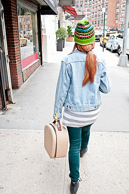 Young woman strolling down street with vanity case - p429m926213 by Angela Cappetta