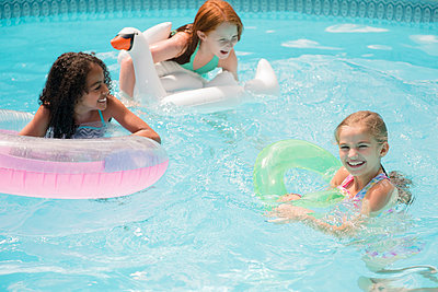 Smiling girls floating in swimming pool - p555m1303501 by JGI/Jamie Grill