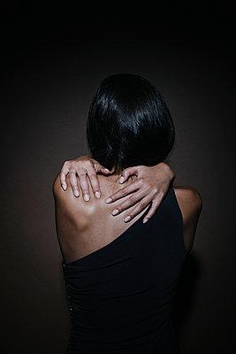Junge Frau mit langen dunklen Haaren posiert, Rückansicht - p586m953774 von Kniel Synnatzschke