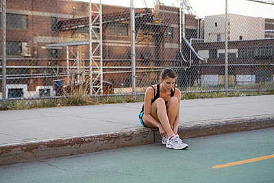 Female runner sitting on sidewalk - p9245287f by Image Source