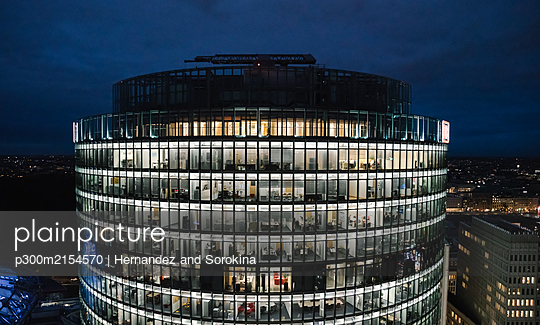 View to lighted modern office building at night, Potsdamer Platz, Berlin, Germany - p300m2154570 by Hernandez and Sorokina