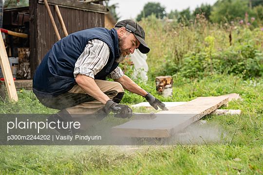 Carpenter brushing plank with wire brush - p300m2244202 by Vasily Pindyurin