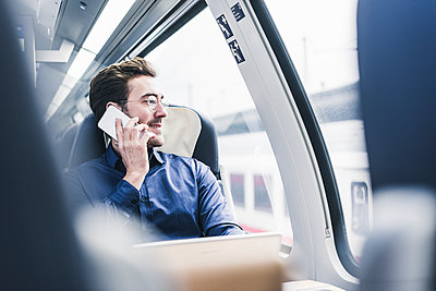 Smiling businessman in train on cell phone - p300m1563296 by Uwe Umstätter