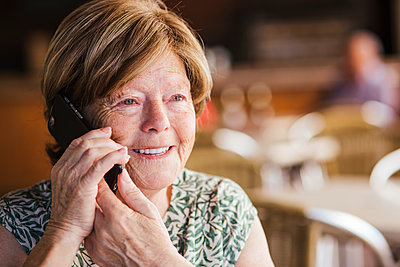 Smiling woman talking on mobile phone while sitting at cafe - p300m2226058 by DREAMSTOCK1982