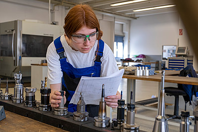 Female technician working with metallic machinery parts while reading book at workshop - p300m2290604 by Lisa und Wilfried Bahnmüller