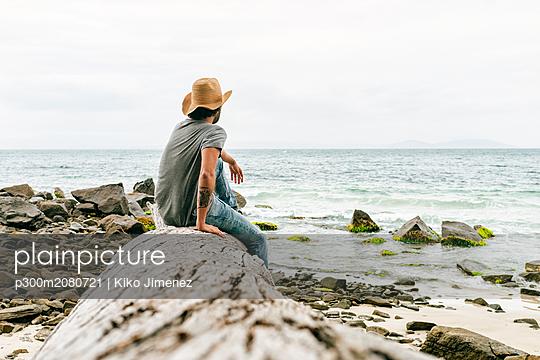 Australia, Tasmania, Maria Island, back view of man sitting on a rock looking at view - p300m2080721 by Kiko Jimenez