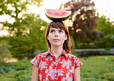 Frau balanciert Wassermelone auf dem Kopf - p1124m1134797 von Willing-Holtz