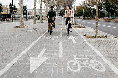 Couple riding e-bikes in the city on bicycle lane - p300m2103946 von Josep Rovirosa