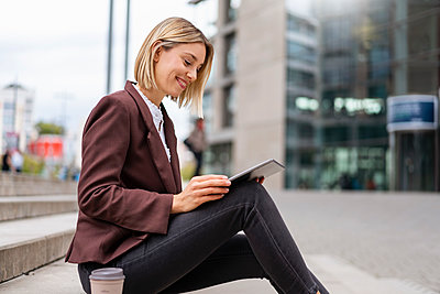 Smiling young businesswoman using tablet in the city - p300m2143485 by Daniel Ingold