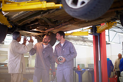 Two car mechanics with client in repair garage - p300m975566f by zerocreatives