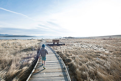 Rear view of boy walking alone on boardwalk across grass in front of Mono Lake, California, USA - p343m1490634 by Alasdair Turner / Aurora Photos