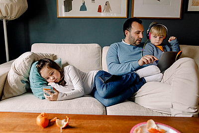 Girl using mobile phone while father showing digital tablet to sister on couch in living room at home - p426m2074491 by Maskot