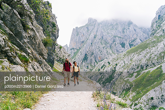 Man and woman hiking together on mountain path at Ruta Del Cares, Asturias, Spain - p300m2213966 by Daniel González