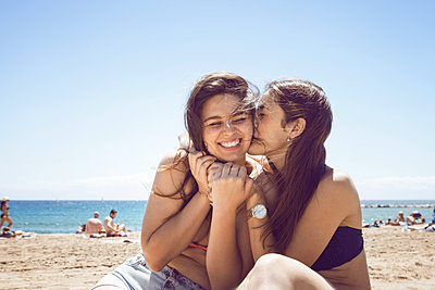 Happy woman kissing friend while sitting at beach against clear sky - p1166m1182810 by Cavan Images