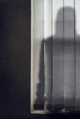 Shadow of man behind blinds - p1280m2126812 by Dave Wall