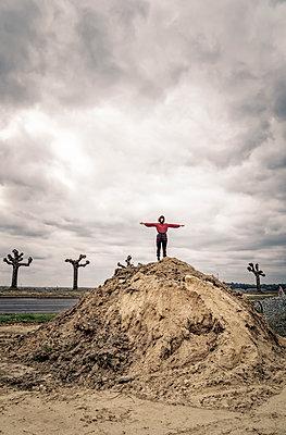 Girl on soil mound - p1402m2260803 by Jerome Paressant