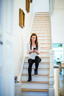 Smiling woman sitting on stairs at home using cell phone - p300m1587839 von Robijn Page