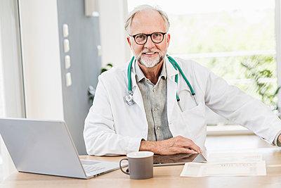 Smiling mature male doctor at desk - p300m2293811 by Uwe Umstätter