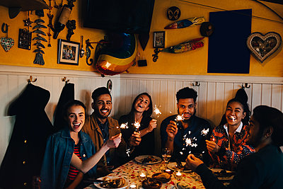 Portrait of cheerful young multi-ethnic friends sitting with burning sparklers at table in restaurant - p426m2046296 by Maskot