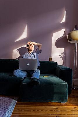 Frau sitzt mit Laptop auf dem Sofa - p432m2172094 von mia takahara