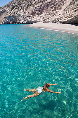 Female tourist swimming in the clear, turquoise water of Galazia Nera Bay; Polyaigos Island, Cyclades, Greece - p442m2154157 by Richard Maschmeyer