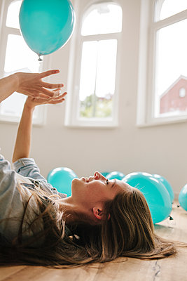 Young woman in new apartment playing with balloons - p586m1064900 by Kniel Synnatzschke
