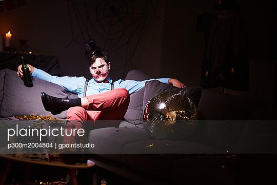 Man in Halloween costume sitting on couch after party, drinking beer - p300m2004804 von gpointstudio