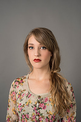 Attractive young, teenage female with long hair worn on one side, wearing floral dress. - p1433m1563443 by Wolf Kettler