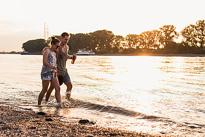 Happy young couple wading in river at sunset - p300m2023790 by Uwe Umstätter