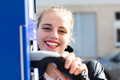 Portrait of young beautiful blonde posing at gas station with fuel pump in hand - p300m2267427 by Sigrid Gombert
