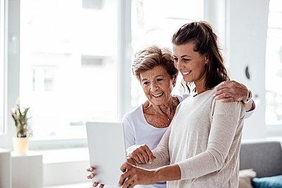 Happy woman taking selfie with grandmother at home - p300m2276968 by Gustafsson