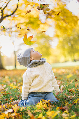 Little boy playing in autumn leaves in Sweden - p352m1536619 by Calle Artmark