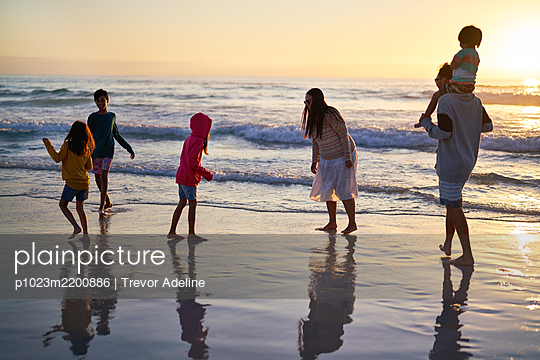 Family playing in ocean surf at sunset - p1023m2200886 by Trevor Adeline