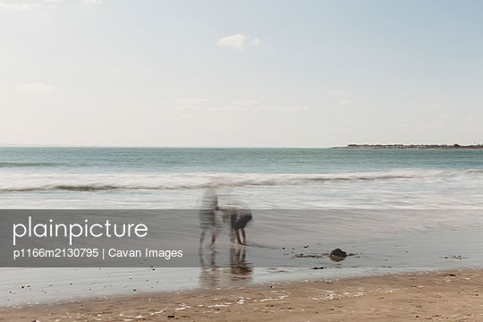 Long exposure of children playing on beach - p1166m2130795 by Cavan Images
