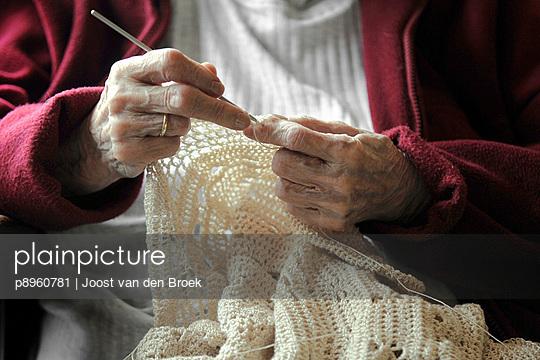 Senior woman knitting - p8960781 by Joost van den Broek
