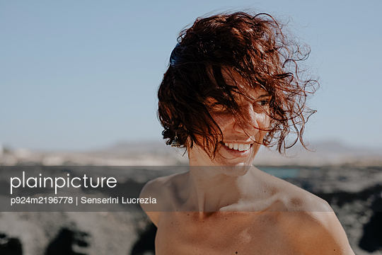 Head and shoulders portrait of smiling woman with brown curly hair on Fuerteventura. - p924m2196778 by Senserini Lucrezia