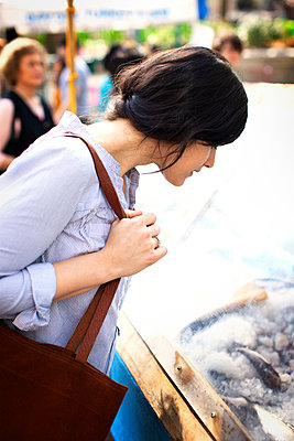 Side view of woman shopping for fish at market stall - p1166m995203f by Cavan Images
