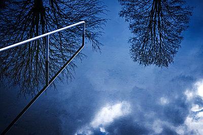 Geländer an einem Badesee mit Spiegelung der Baumkronen im Wasser  - p1312m2161003 von Axel Killian