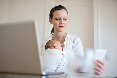 Mother with baby girl in sling working from home - p300m1228125 by Daniel Ingold