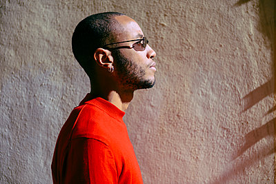 Profile of young man wearing sunglasses and red pullover at sunlight - p300m2070638 von Javier Sánchez Mingorance