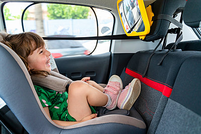 Laughing toddler girl sitting in a car seat looking in a mirror - p300m2139880 by Gemma Ferrando
