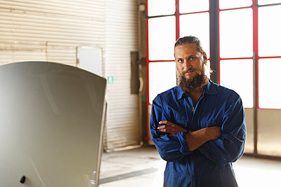 Mechanic posing next to a car in a workshop in Sweden - p352m2040757 by Christian Ferm