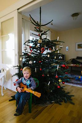 Kleiner Junge mit Spielzeuggitarre am Weihnachtsbaum - p819m1065051 von Kniel Mess