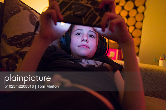 Girl with headphones using smart phone on sofa - p1023m2208316 by Tom Merton