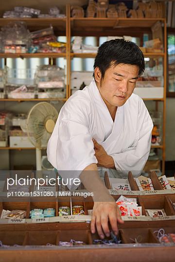 Salesman wearing white kimono at Shinto Sakurai Shrine, Fukuoka, Japan. - p1100m1531080 by Mint Images